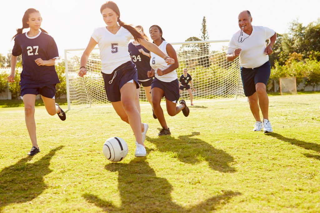 Members Of Female High School Soccer Playing Match