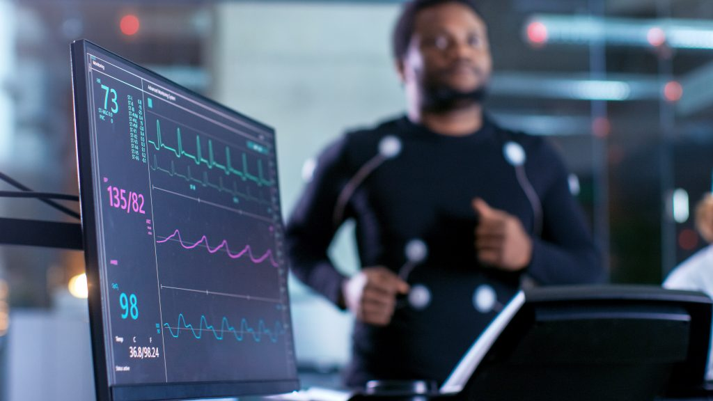 Close-up Shot of a Monitor With EKG Data. Male Athlete Runs on a Treadmill with Electrodes Attached to His Body while Sport Scientist Holds Tablet and Supervises EKG Status in the Background.