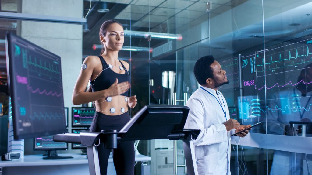 Beautiful Woman Athlete Runs on a Treadmill with Electrodes Attached to Her Body, Physician Uses Tablet Computer and Controls EKG Data Showing on Laboratory Monitors.